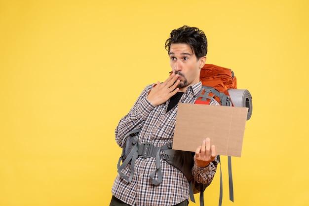 Vooraanzicht jonge man gaat wandelen met rugzak op gele achtergrond vliegreis natuur campus bos emotie bedrijfskaart
