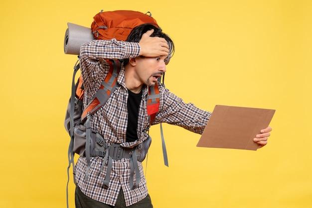 Vooraanzicht jonge man gaat wandelen met rugzak op gele achtergrondkleur vliegreis natuur campus bos emotie bedrijfskaart