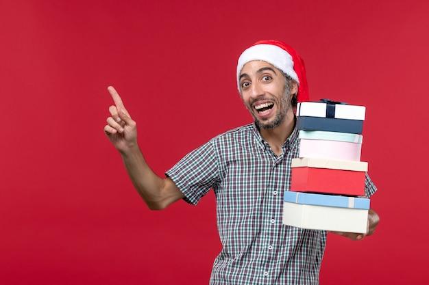 Vooraanzicht jonge man gelukkig bedrijf presenteert op rode achtergrond