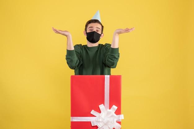 Vooraanzicht jonge man handen openen achter grote geschenkdoos op geel