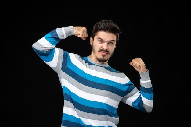 Vooraanzicht jonge man in blauw gestreepte jersey buigen