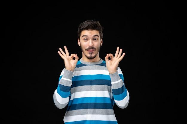 Vooraanzicht jonge man in blauw gestreepte trui die een goed gebaar doet