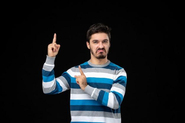 Vooraanzicht jonge man in blauw gestreepte trui die omhoog wijst