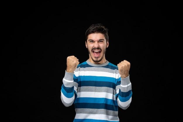 Vooraanzicht jonge man in blauw gestreepte trui die zich verheugt op de zwarte muur