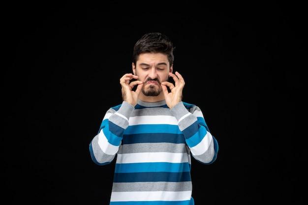 Vooraanzicht jonge man in blauw gestreepte trui die zijn snor verzorgt
