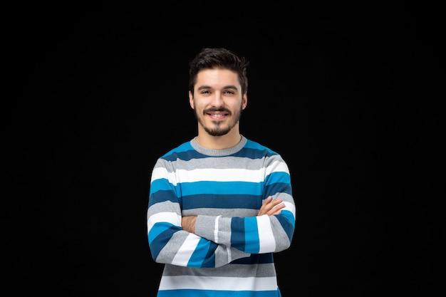 Vooraanzicht jonge man in blauw gestreepte trui glimlachend op zwarte muur