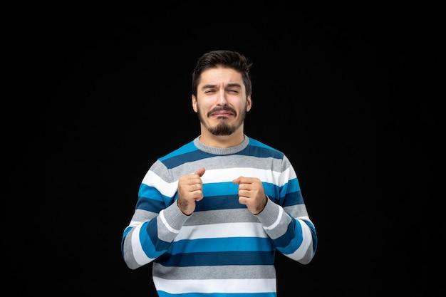 Vooraanzicht jonge man in blauw gestreepte trui huilend