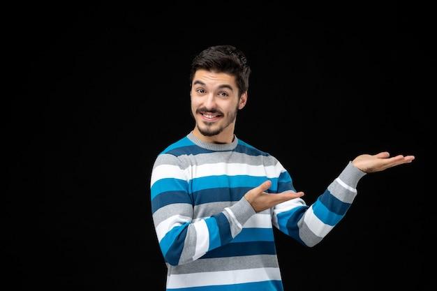 Vooraanzicht jonge man in blauw gestreepte trui met een product