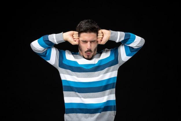 Vooraanzicht jonge man in blauw gestreepte trui met hoofdpijn