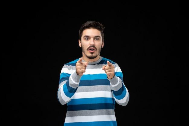 Vooraanzicht jonge man in blauw gestreepte trui met verrast gezicht op zwarte muur