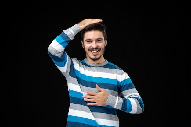 Vooraanzicht jonge man in blauw gestreepte trui op de zwarte muur foto kleur emotie duisternis menselijk model