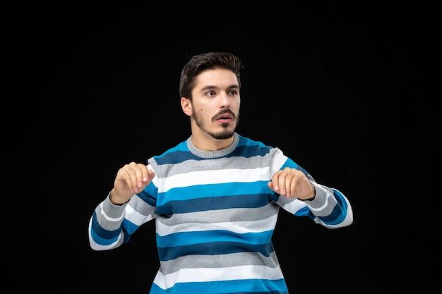 Vooraanzicht jonge man in blauw gestreepte trui op de zwarte muur