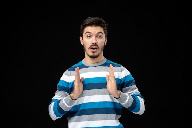 Vooraanzicht jonge man in blauw gestreepte trui op zwarte muur model foto man emotie