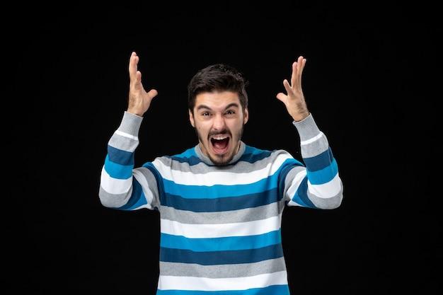 Vooraanzicht jonge man in blauw gestreepte trui schreeuwen op zwarte muur