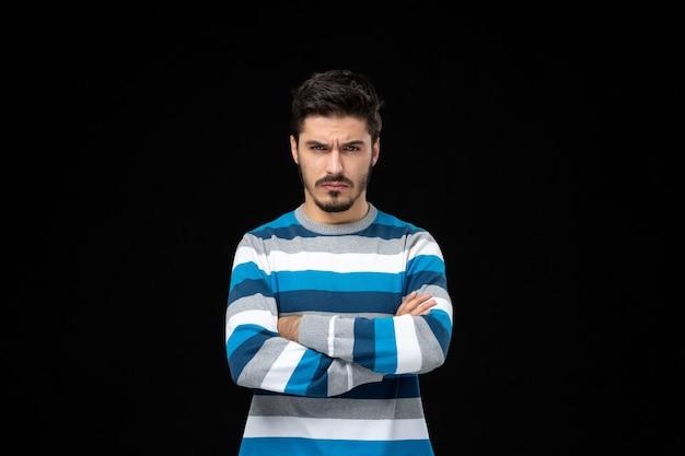 Vooraanzicht jonge man in blauw gestreepte trui staren met gekruiste armen