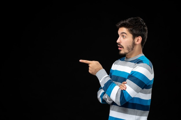 Vooraanzicht jonge man in blauw gestreepte trui wijzend op kopieerruimte