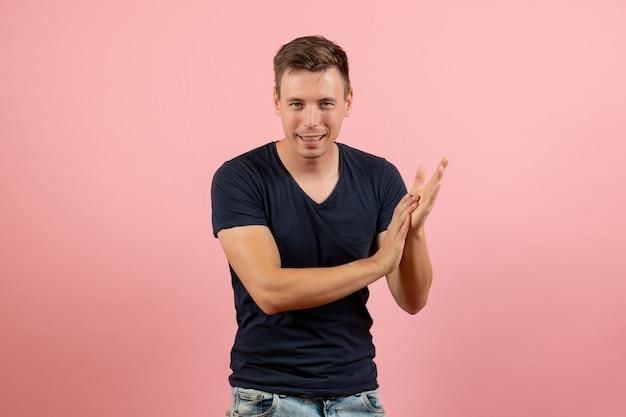Vooraanzicht jonge man in blauw t-shirt poseren klappen op roze achtergrond man model emotie kleur man