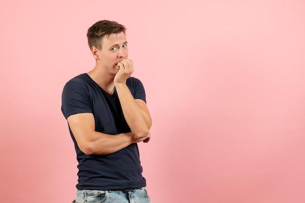 Vooraanzicht jonge man in blauw t-shirt zijn nagels bijten van zenuwen op roze achtergrond emotie kleur model menselijke man