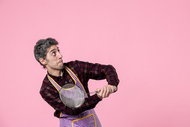 Vooraanzicht jonge man in cape die zeef vasthoudt en opzij kijkt op roze achtergrondkleur kok uniform echtgenoot werknemer baan horizontaal voedsel keuken