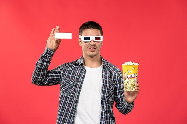 Vooraanzicht jonge man in -d zonnebril met popcornpakket en kaartje op lichte rode muur bioscoop films theater film mannetje