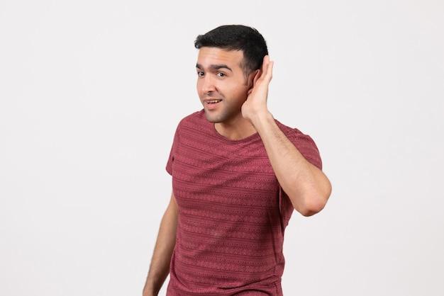 Vooraanzicht jonge man in donkerrood t-shirt die staat en probeert te horen op een witte achtergrond
