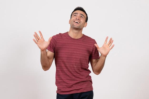 Vooraanzicht jonge man in donkerrood t-shirt poseren op lichte witte achtergrond