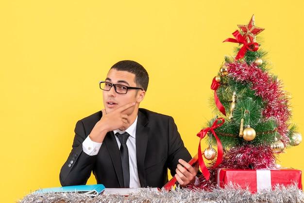 Vooraanzicht jonge man in een pak zitten aan de tafel zetten hand