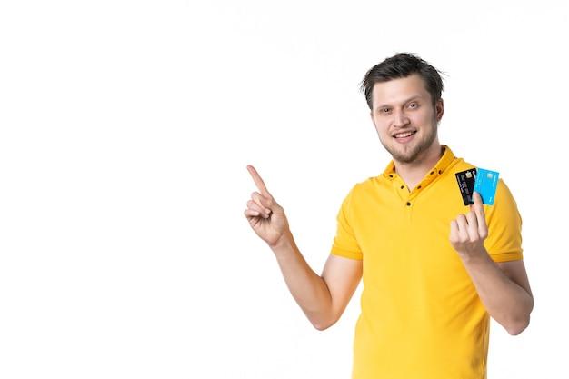 Vooraanzicht jonge man in geel shirt met paar bankkaarten op de witte muur uniforme baan geld kleur menselijke werknemer uitgaven verkoper sales
