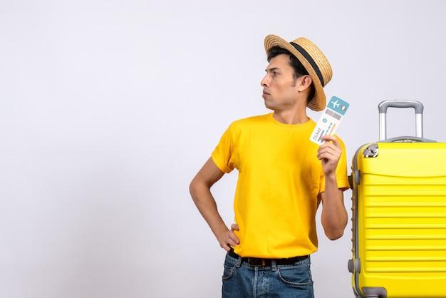Vooraanzicht jonge man in geel t-shirt staande in de buurt van gele koffer hand op een taille te zetten