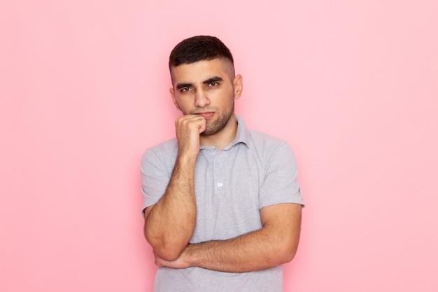 Vooraanzicht jonge man in grijs shirt poseren met denken staan op roze