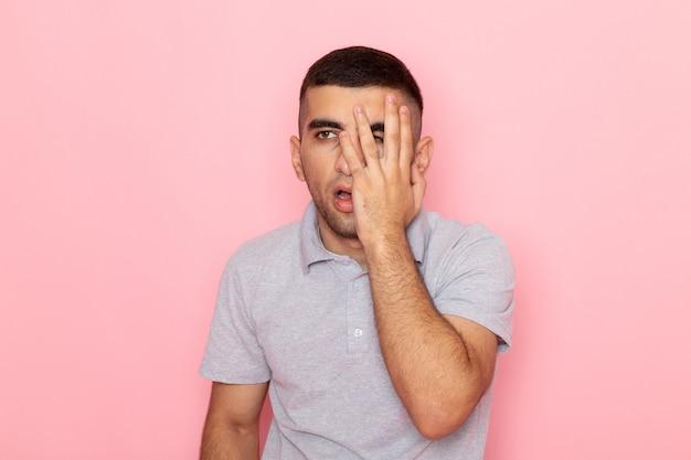 Vooraanzicht jonge man in grijs shirt poseren met teleurgestelde uitdrukking op roze