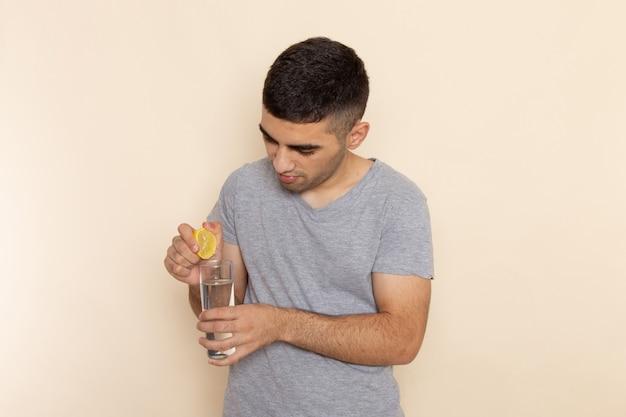 Vooraanzicht jonge man in grijs t-shirt citroensap op beige te drukken