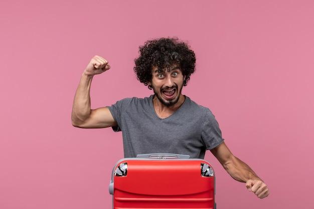 Vooraanzicht jonge man in grijs t-shirt die zich voorbereidt op een reis die zich verheugt op roze ruimte