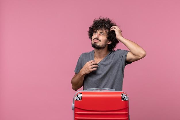 Vooraanzicht jonge man in grijs t-shirt die zich voorbereidt op een reis op de roze ruimte