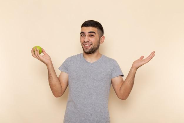 Vooraanzicht jonge man in grijs t-shirt en spijkerbroek glimlachend en appel op beig te houden