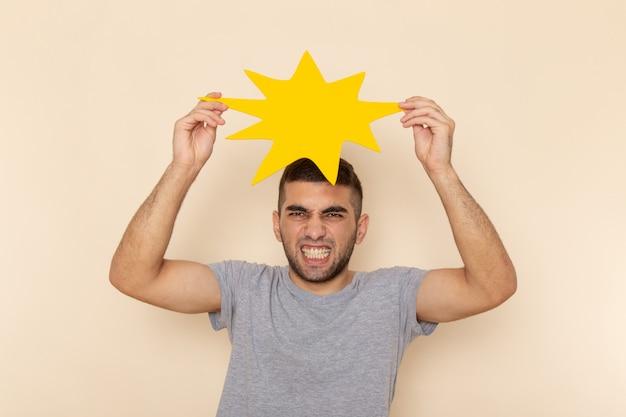 Vooraanzicht jonge man in grijs t-shirt en spijkerbroek met geel bord op beige