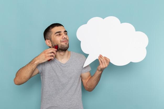 Vooraanzicht jonge man in grijs t-shirt met een groot wit bord en elektrisch scheerapparaat op de ijsblauwe muur baard schuim haar scheermes scheren