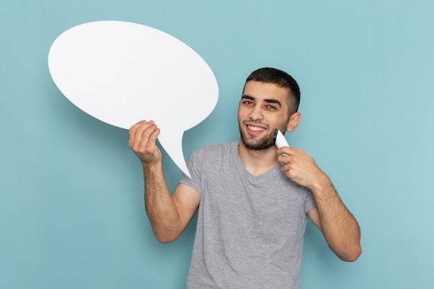 Vooraanzicht jonge man in grijs t-shirt met elektrisch scheerapparaat met wit bord glimlachend op ijsblauw