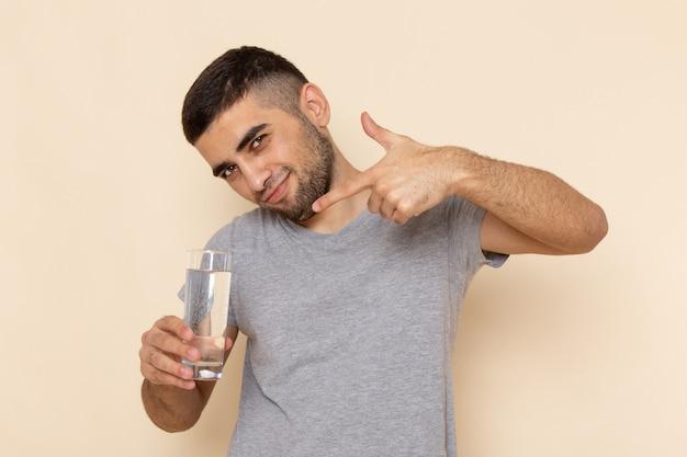 Vooraanzicht jonge man in grijs t-shirt met glas water op beige