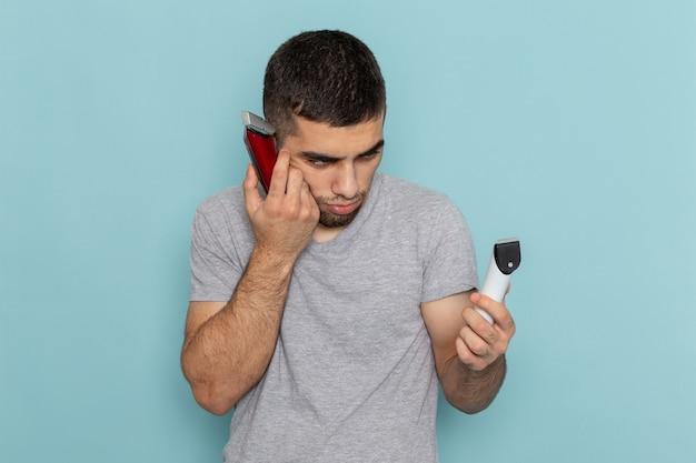 Vooraanzicht jonge man in grijs t-shirt met twee verschillende elektrische scheerapparaten, denkend welke te kiezen