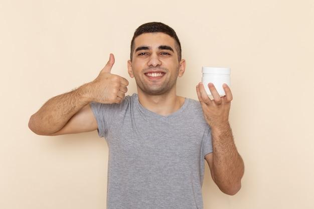 Vooraanzicht jonge man in grijs t-shirt met wit kan met glimlach op beige