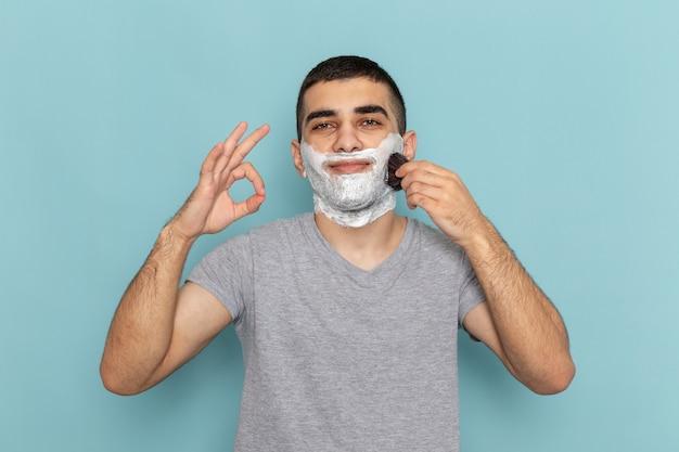 Vooraanzicht jonge man in grijs t-shirt met wit schuim op zijn gezicht wrijven met borstel op ijsblauw
