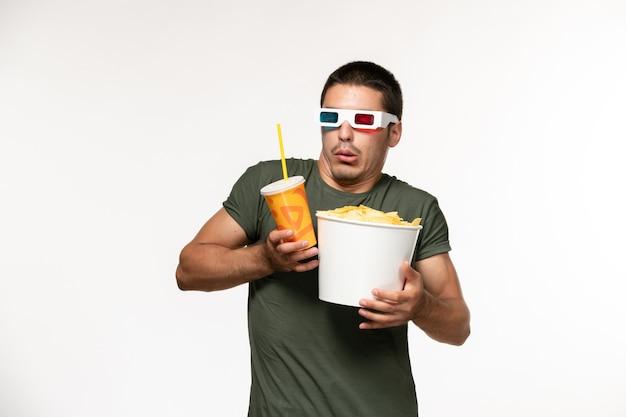 Vooraanzicht jonge man in groen t-shirt met aardappel cips frisdrank in d zonnebril op lichte witte muur film mannelijke eenzame film bioscoop