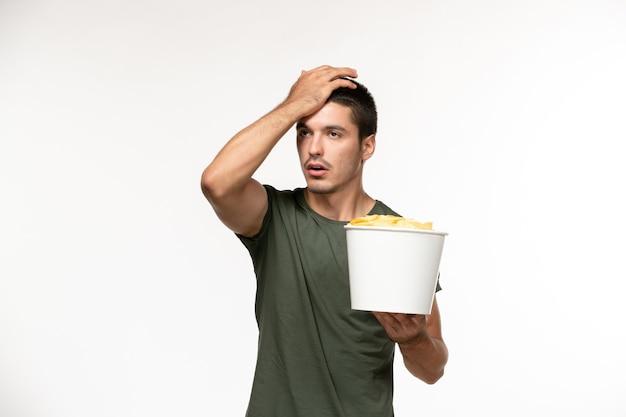 Vooraanzicht jonge man in groen t-shirt met aardappel cips op lichte witte muur eenzame film film bioscoop persoon