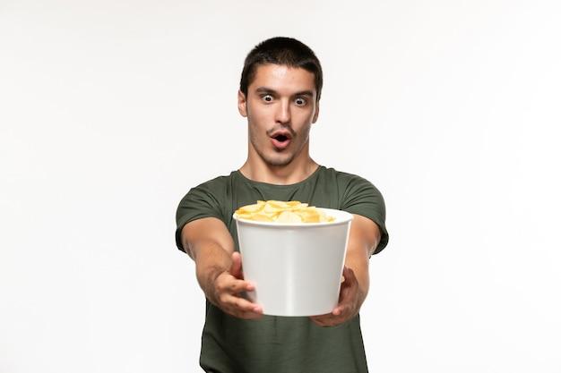 Vooraanzicht jonge man in groen t-shirt met aardappel cips op witte muur eenzame film film bioscoop persoon