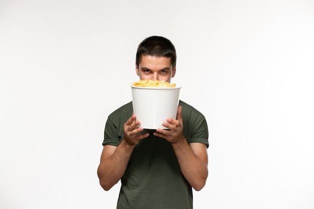 Vooraanzicht jonge man in groen t-shirt met aardappel cips op witte muur persoon eenzame film film bioscoop