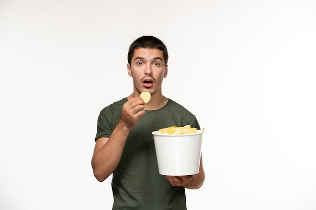 Vooraanzicht jonge man in groen t-shirt met aardappel cips op witte muur persoon eenzame film films bioscoop