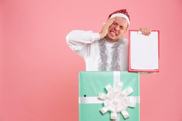 Vooraanzicht jonge man in huidige bestand notities en lijden aan hoofdpijn op roze achtergrond