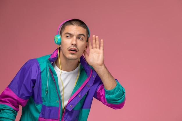Vooraanzicht jonge man in kleurrijke jas luisteren naar muziek proberen te horen op de roze achtergrond
