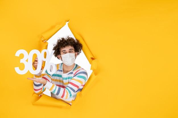 Vooraanzicht jonge man in masker met gele kleur winkelen gezondheid covid- foto pandemische virusverkoop